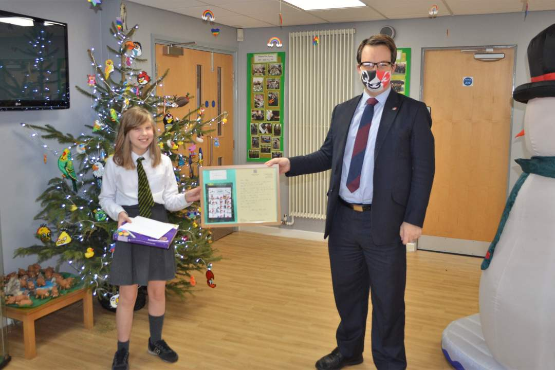 Mike presenting prizes to Christmas card competition-winner Holly Barnes of Ashwood Park Primary School